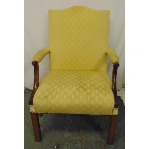 36 - A mahogany high back upholstered armchair on four rectangular legs...