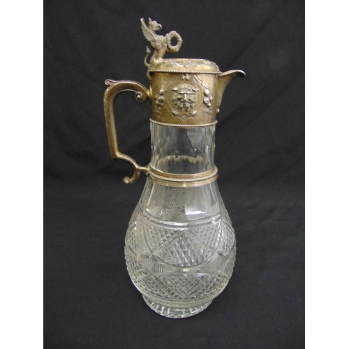 406 - A Victorian hobnail cut glass claret jug, the silver collar chased with masks and fruit with leaf en...