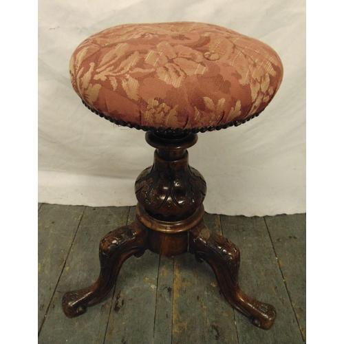 43 - A Victorian piano stool on three scroll legs...