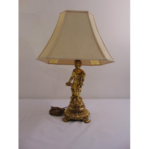 54 - A gilded metal table lamp in the form of a putti on raised circular base with silk shade...