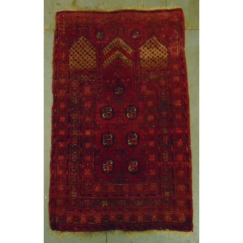 55 - A Middle Eastern wool carpet red ground with repeating geometric patterns, 121 x 75.5cm...