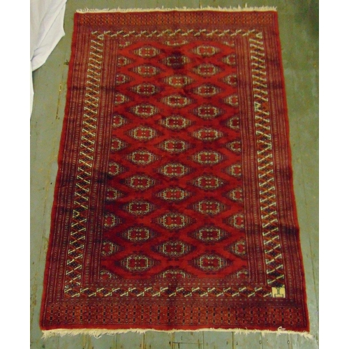 56 - A Middle Eastern wool carpet red ground with repeating geometric forms and stylised border, 179 x 12...
