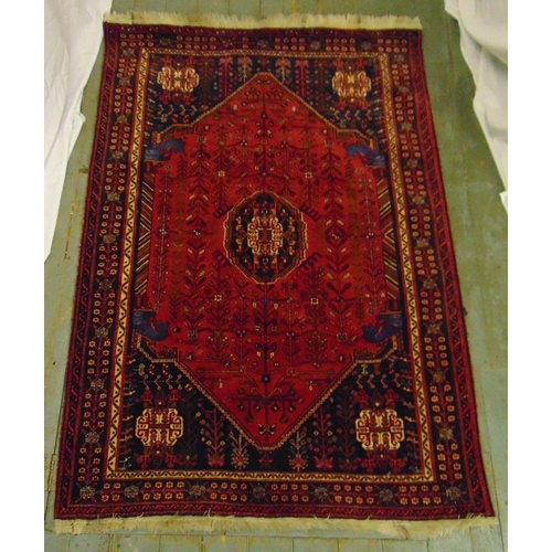 57 - A Qashqai carpet red and black ground with stylised motifs and repeating patterns, 188 x 134cm...