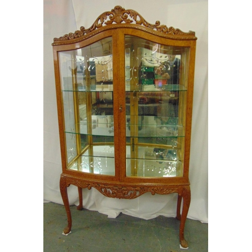 8 - An Epstein bow fronted rectangular glazed display cabinet with scroll pierced top on cabriole legs...