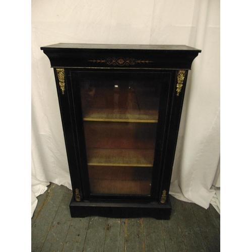 10 - A rectangular ebonised and glazed display cabinet on raised rectangular plinth with brass mounts...