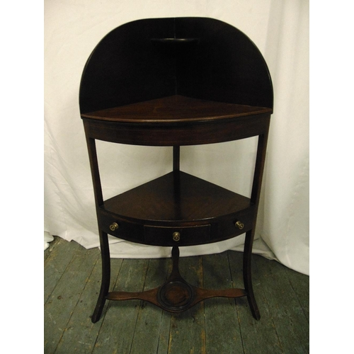 13 - A Sheraton style mahogany corner stand on three outswept supports and a single drawer with turned br...