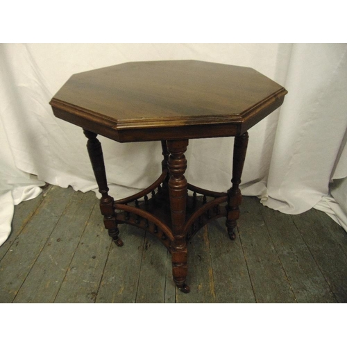 14 - An Edwardian octagonal mahogany gallery side table on turned legs and castors...
