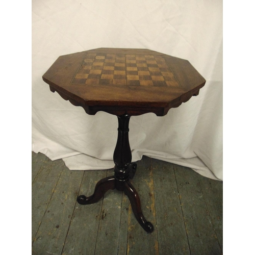18 - A Victorian mahogany octagonal games table the top inlaid with a chequer board, on a baluster stem a...