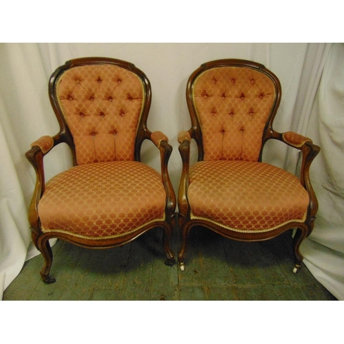21 - A pair of Victorian mahogany upholstered armchairs on cabriole legs...
