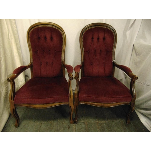 22 - A pair of mahogany button back upholstered armchairs on scroll legs...
