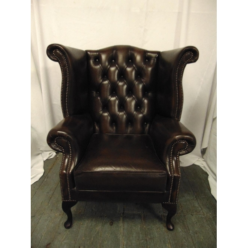 24 - A leather wing back armchair on four scroll legs...
