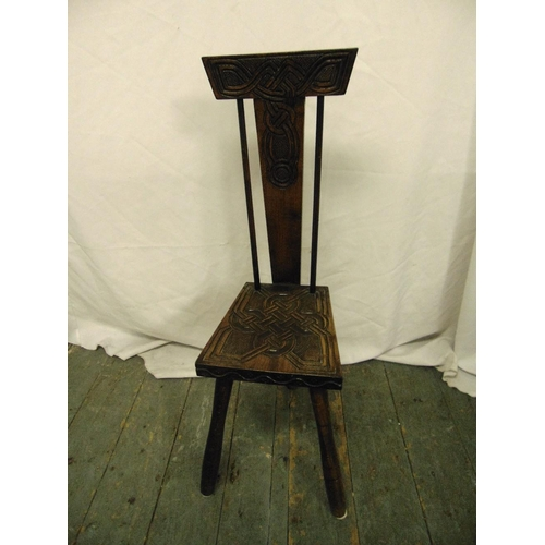 29 - A Victorian oak milking chair with T-form geometric back, carved seat and cylindrical legs...