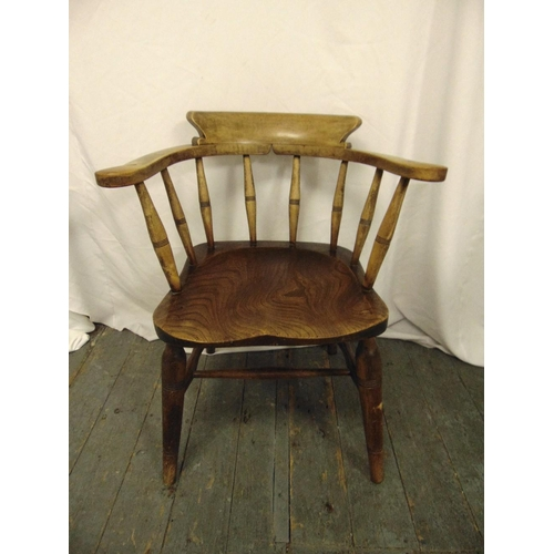 31 - An elm Windsor chair of customary form with turned spindles on four turned legs...