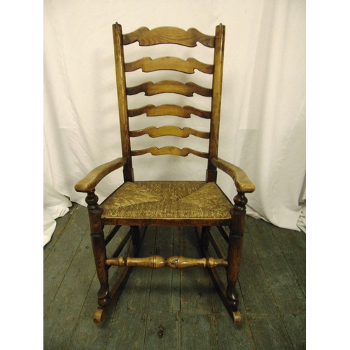 32 - An oak rocking chair with scrolling arms and rush seat...