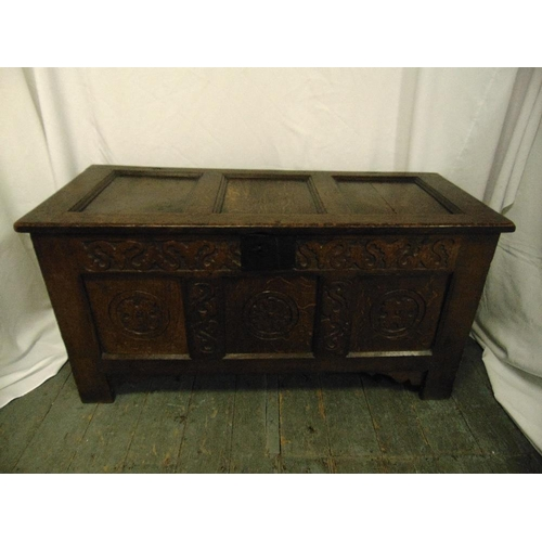 34 - An early rectangular oak coffer with carved side panels, hinged cover and bracket feet...
