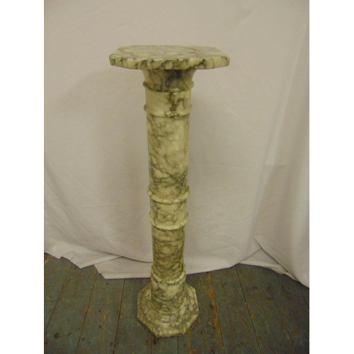 37 - A marble column plant stand of ribbed cylindrical form with octagonal top and base...