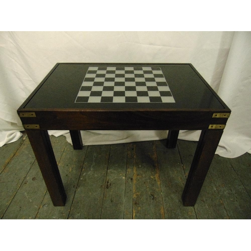 38 - A 1960s mahogany rectangular games table the glass sliding top opening to reveal a compendium of gam...