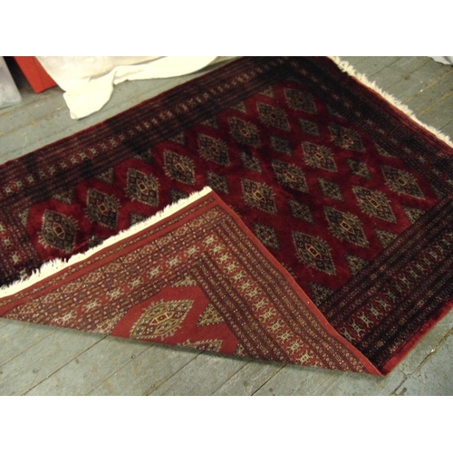 41 - A Persian wool carpet red ground with geometric patterns and border, 231 x 176cm...