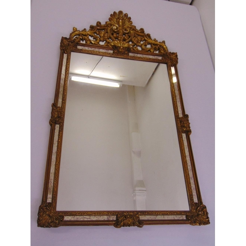 44 - A decorative rectangular gilded wooden wall mirror surmounted by a pierced and carved floral design...
