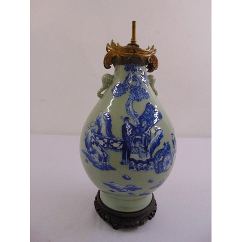 45 - A Chinese 19th century green ground pear shaped vase decorated with figures in a landscape on carved...