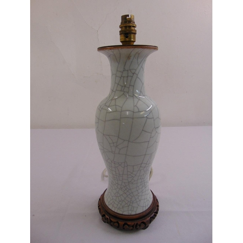 46 - A Chinese Ge type crackle glaze baluster vase converted to a table lamp mounted on a pierced hardwoo...