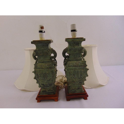 48 - A pair of Chinese style bronze table lamps on raised wooden plinths with silk shades...