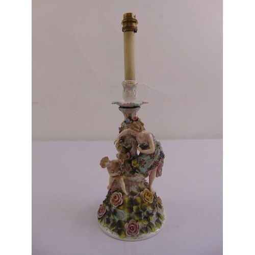 53 - A continental porcelain table lamp figural group amidst flowers and leaves on circular base...