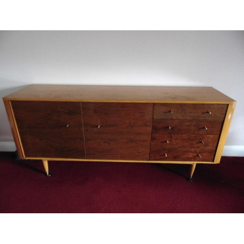 6 - A rectangular yew wood sideboard with four drawers and two cupboards on four tapering cylindrical le...