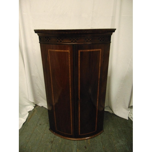 8 - A 19th century mahogany inlaid wall mounted corner cabinet with hinged doors...