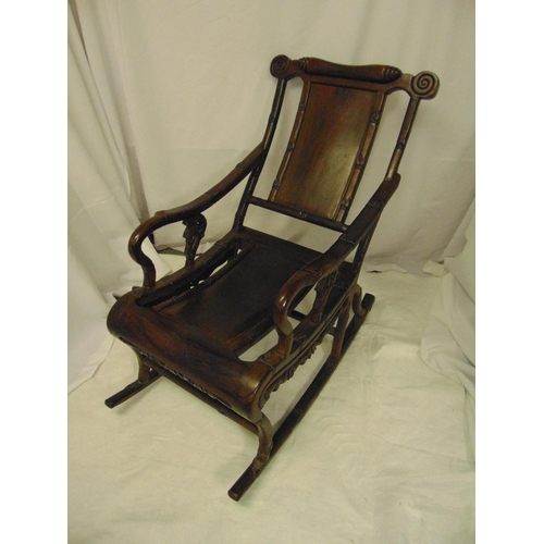 1 - Chinese hardwood rocking or moon chair of simulated bamboo form with scrolling arms and runners...