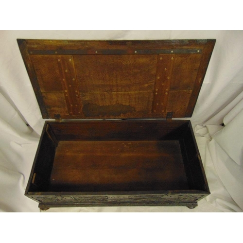 11 - A rectangular oak blanket box with carved 17th century side panels hinged cover on four bun feet...
