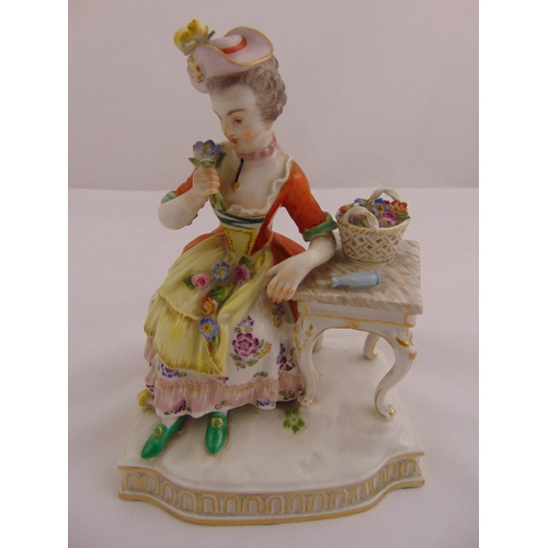 116 - Meissen figurine of a lady holding flowers seated next to a table, on shaped rectangular plinth, mar...