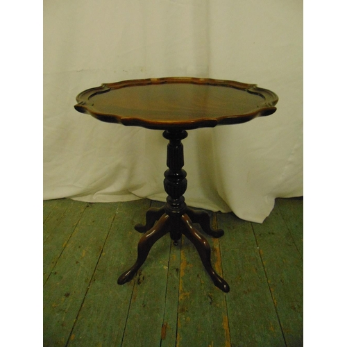 14 - A mahogany wine table with moulded border, baluster stem and four scroll legs...