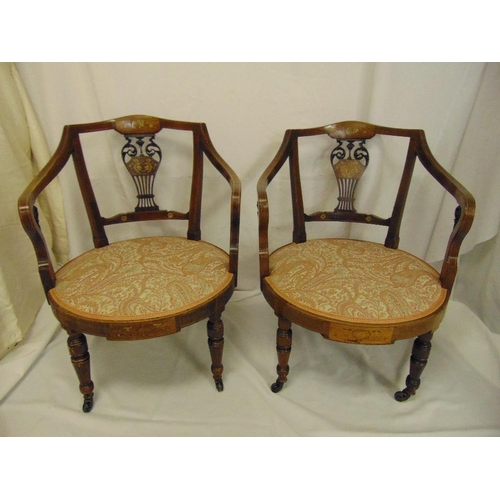 20 - A pair of Edwardian mahogany inlaid upholstered armchairs on four turned tubular legs...
