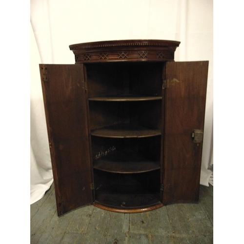 6 - A mahogany inlaid wall mounted corner cabinet with hinged doors...