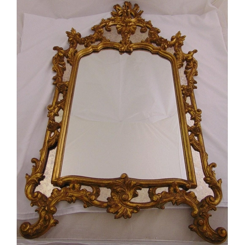 27 - A gilded wooden Rococo style hall mirror of pierced rectangular form, 137 x 83cm...
