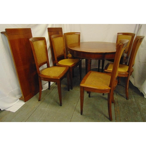 7 - A mahogany circular dining table with two drop in leaves and six matching caned dining chairs, 78 x ...