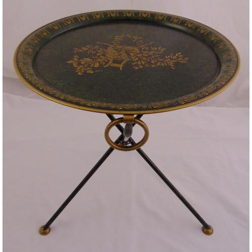 28 - An Italian Toleware folding table, circular with gilt decoration on three tubular supports, 48.5 x 4...