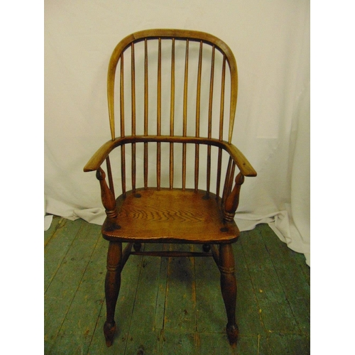 11 - A 19th century oak Windsor chair on turned cylindrical legs...