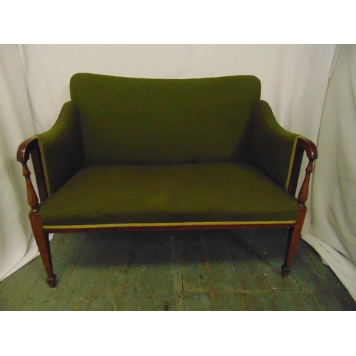 12 - An Edwardian two seater settle with upholstered seat and back on tapering rectangular legs...