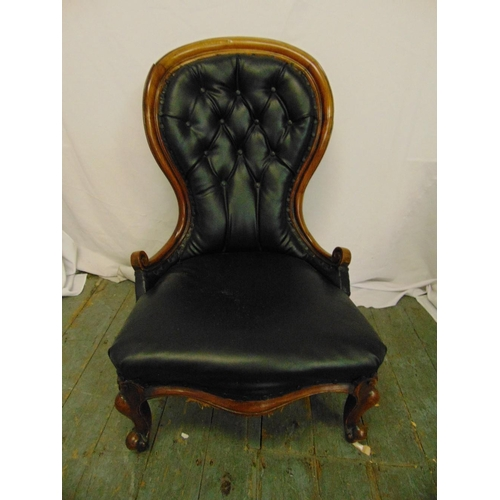 13 - A Victorian black leather button back ladies chair on scroll legs...
