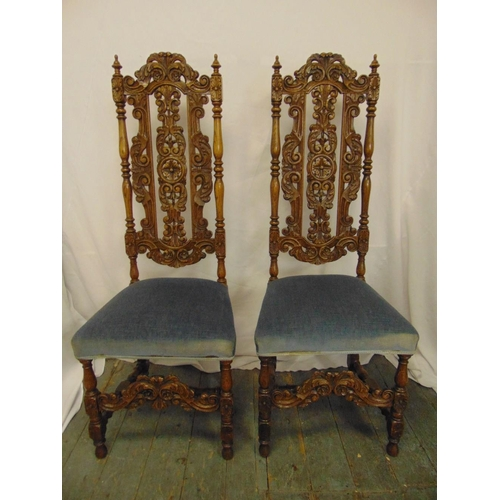 14 - A pair of continental profusely carved and pierced high back upholstered occasional chairs on four t...