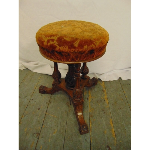 18 - An oak piano stool with upholstered seat on triform base...