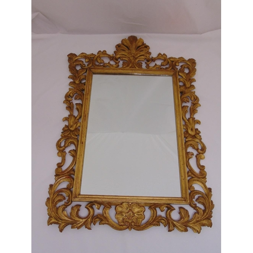 23 - A gilded wooden rectangular, leaf and shell carved wall mirror in the Rococo style, 100 x 68.5cm...