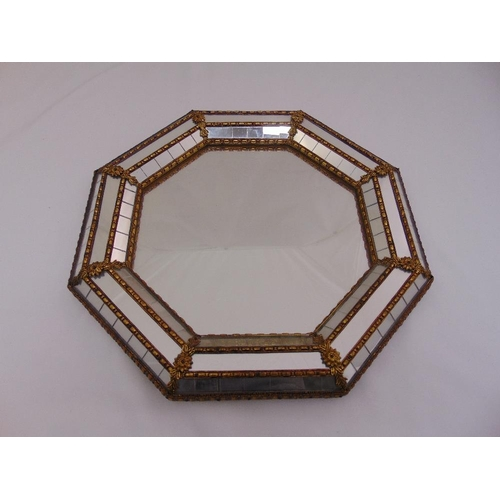 24 - An octagonal gilded metal mounted wall mirror with raised bevelled border, 40.5 diameter...