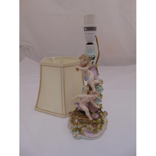 28 - A continental porcelain table lamp in the form of putti and flowers with silk shade...