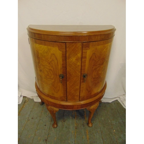 5 - A mahogany and satinwood demi-lune cabinet with hinged doors on four scroll legs...