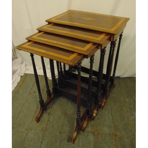 14 - A mahogany and kingswood nest of four rectangular tables on turned cylindrical supports and scroll l...