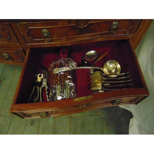 18 - A rectangular mahogany canteen with lion mask handles, the four drawers revealing an extensive colle...