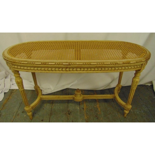 28 - A French oval bergere stool with hand painted detail on four tapering fluted legs, 51 x 90 x 38cm...